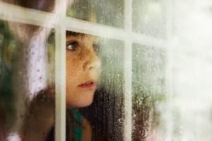 boy-looking-out-window-in-the-rain